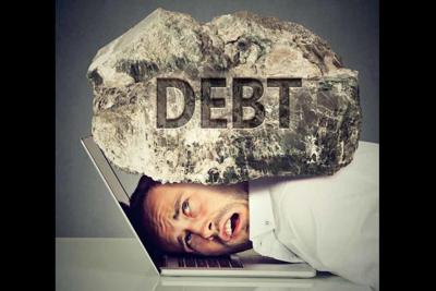 man squeezed between laptop and rock. Student loan debt concept