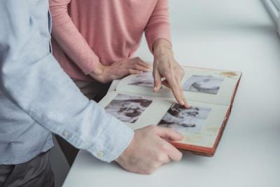 cropped shot of mother and son with photo album together at home