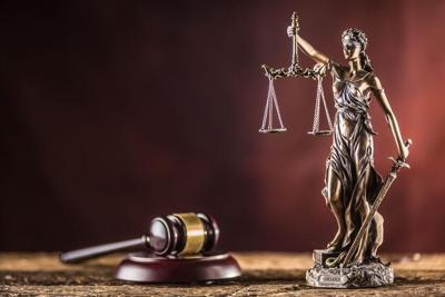 Lady Justicia holding sword and scale bronze figurine with judge hammer on wooden table