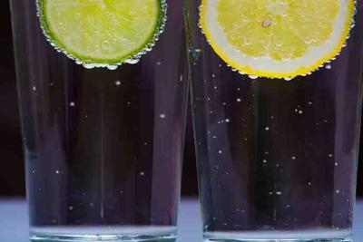 Glass with cold sparkling mineral water, lime and lemon