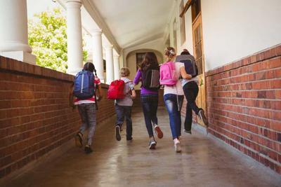 School kids running in school corridor
