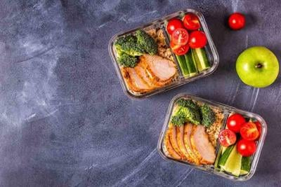 Healthy balanced lunch box with chicken, rice, vegetables.