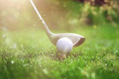 Golfer putting golf ball on the green