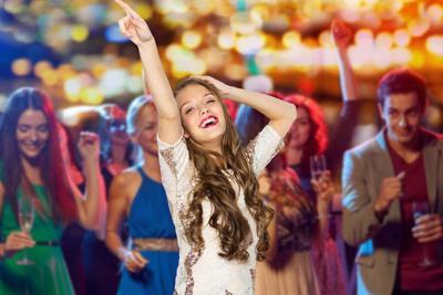 happy young woman dancing at night club
