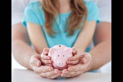 close up of family hands with piggy bank