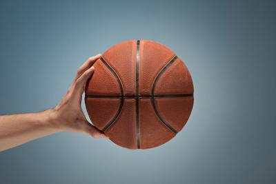Low key shot of a hand holding a basket ball
