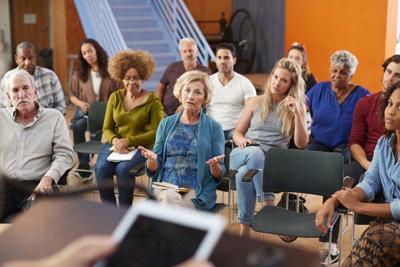 Woman Speaking At Group Neighborhood Meeting In Community Center