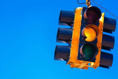 A yellow traffic light with a sky blue background