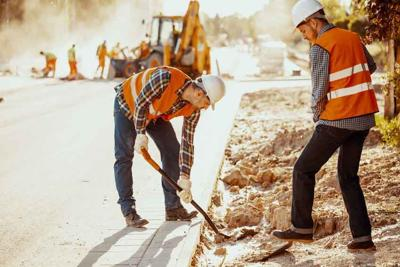 Workers in reflective vests using shovels during carriageway wor