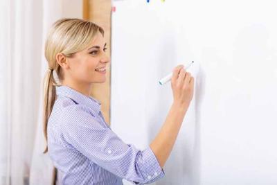 Smiling teacher writing on the whiteboard.