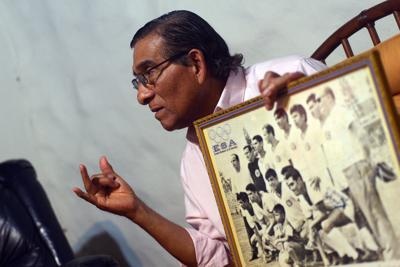 Salvador Mariona, a former soccer player for El Salvador, shows a picture of the national team during the 1970 World Cup.