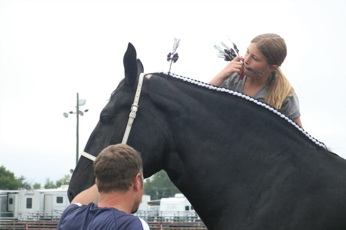 Kynseth Zubrobs of Oklahoma has a mouthful of decor while working on her horse's mane.JPG