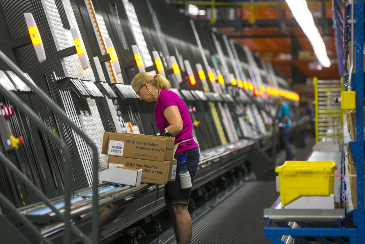 2e9e5e8950 An employee packs a box with medical supplies for shipment Aug. 3, 2016, at  the McKesson pharmaceutical company in Clear Lake. The 340,000 square-foot  ...