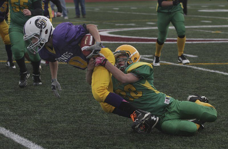 Harrison Marshall of the Riverdale Rockets tackles ball-carrier Hunter Lane of the East Gloucester Vikings during the Cape Ann Pee Wee League A-Team Championships Sunday, Nov. 16, at New Balance Track and Field at Newell Stadium in Gloucester.