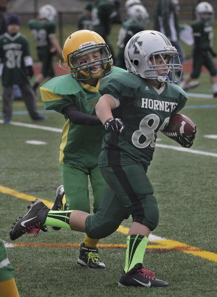 Daniel Wood, right, of the Manchester Essex Junior Hornets hauls in a nine-yard touchdown pass as Frank Desisto tries to chase him down in the Cape Ann Pee Wee Football C-Team Championship Game Sunday, Nov. 16, at New Balance Track and Field at Newell Stadium.
