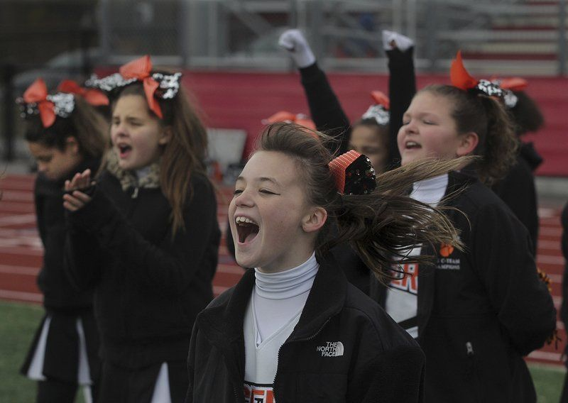 Halley Pepin, 10, and other members of the Hampden Hill Tigers cheerleading squad root for their team during the Cape Ann Pee Wee League B-Team Championships Sunday, Nov. 16, against the Manchester Essex Junior Hornets at Newell Stadium in Gloucester.