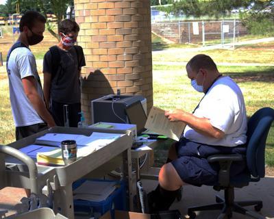 Mark Hofer checking students in (copy)