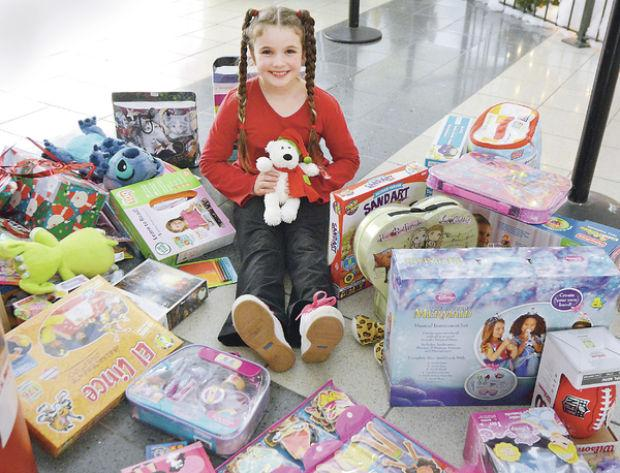 Girl gladly gives gifts to Toys for Tots