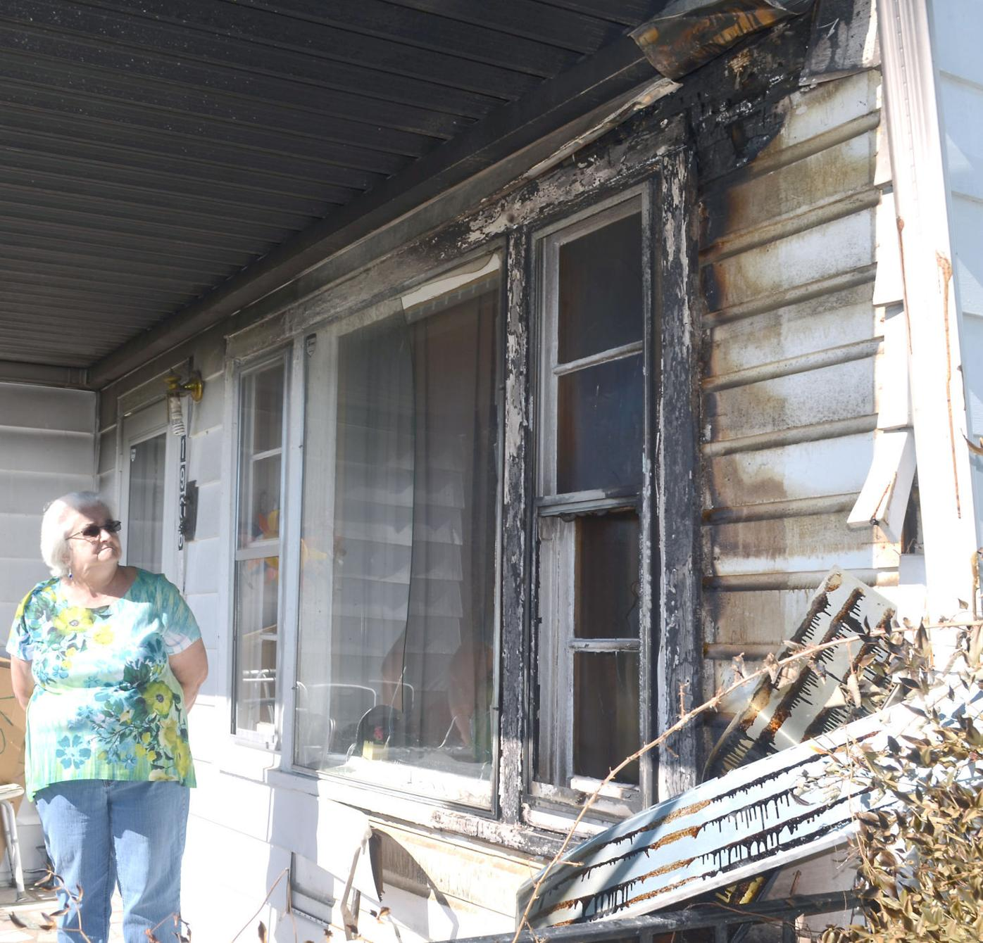 Woman Inspects Fire Damage To Porch