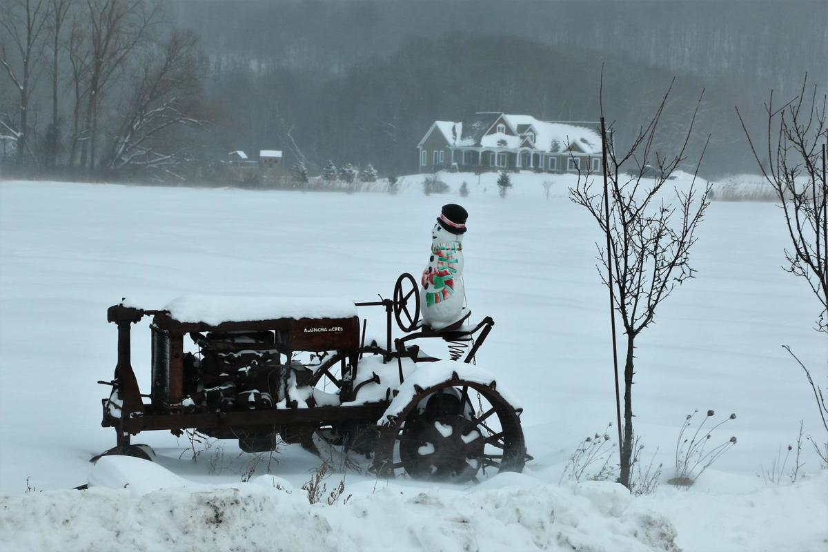 Snowman on a tractor, braving the cold weather