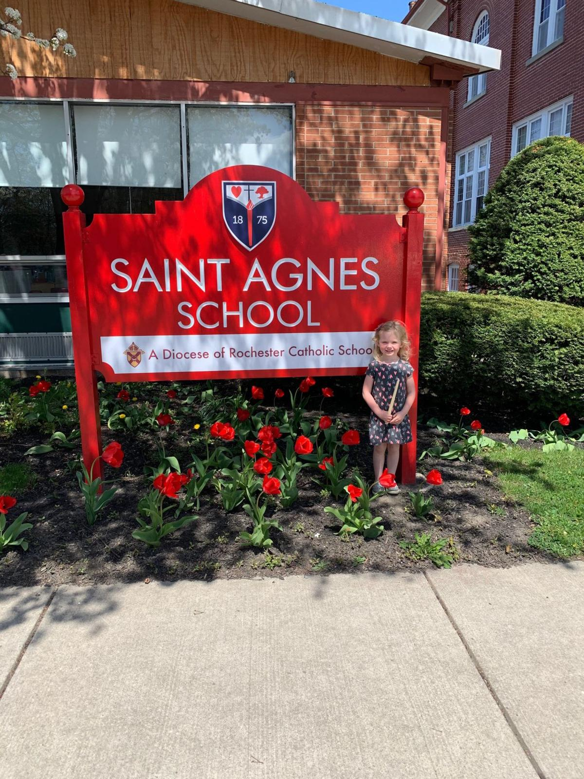 St. Agnes School student, Evie, stands by her school sign.