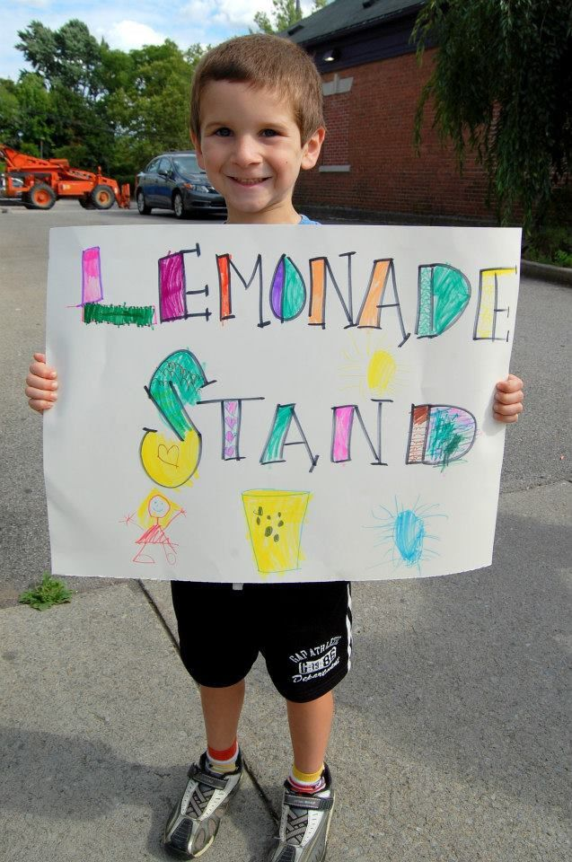 Trevor George holding a lemonade stand sign for a cause!