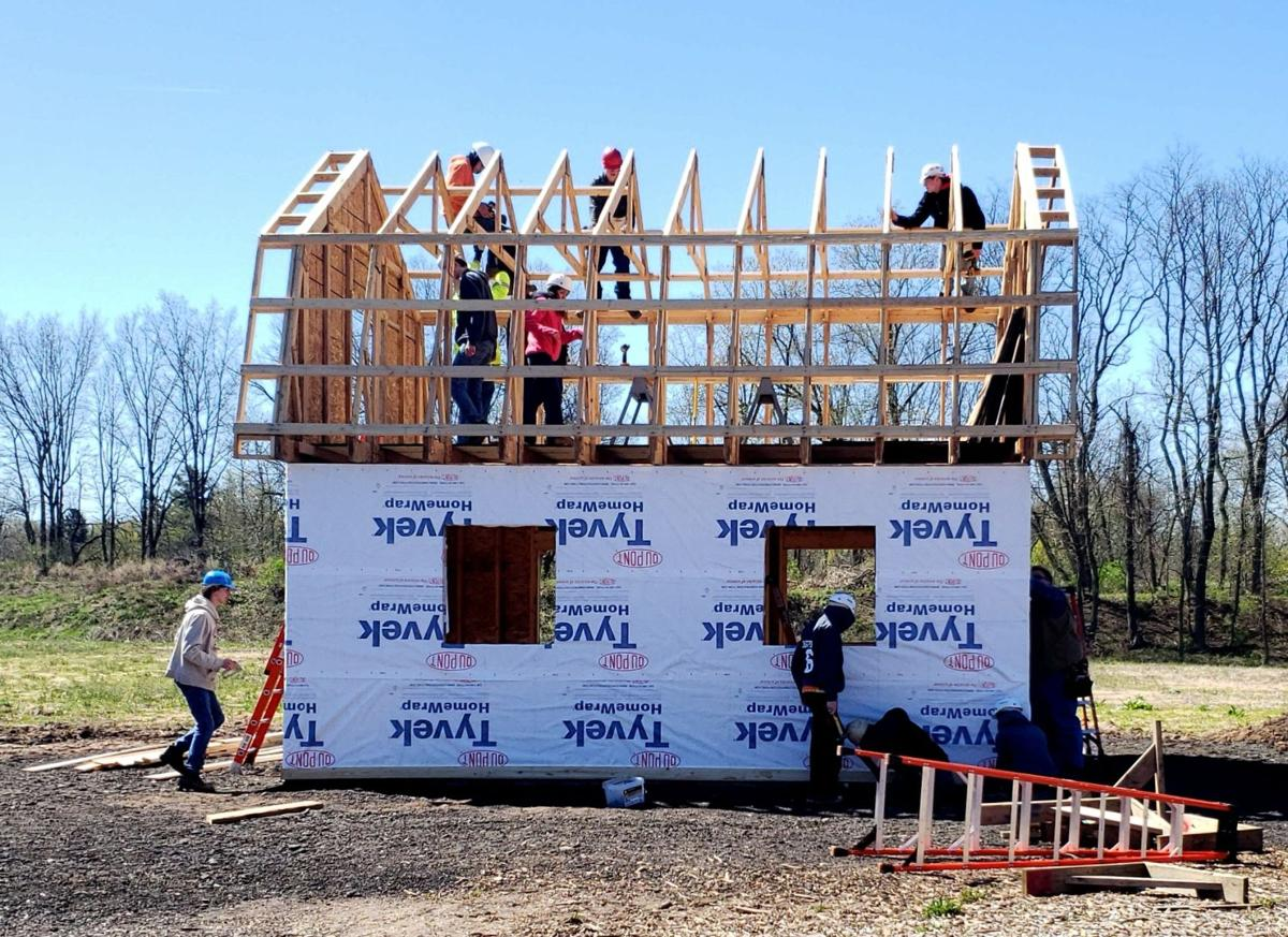 Holley students working on the roof of the barn