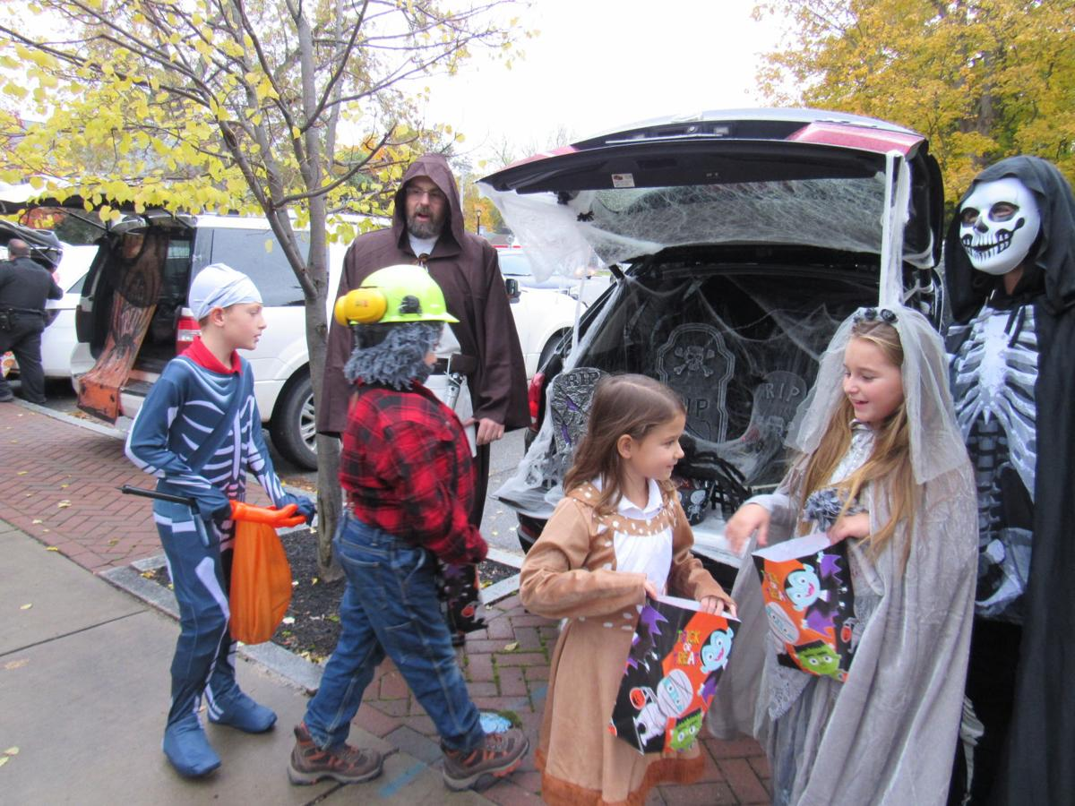 Sawyer Damon, JP Corcoran, Kate Schwan and Hailey Harper get some treats from Randy Harper and Christine Wells Harper at St. Agnes School's Trick or Trunk event