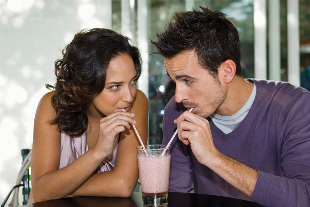Couple drinking from straws