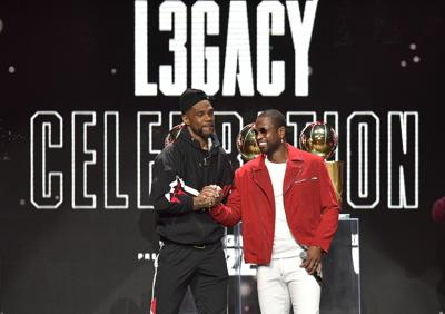 """In this file photo, Dwayn Wade and Udonis Haslem rap to begin the Dwyane Wade Legacy Celebration, Friday, February 21, 2020, at AmericanAirlines Arena. Wade recently said """"people think its easy to bring 15 guys together and win a championship and play as a team. Right now, we're asking the whole country to play as a team. You see how hard it is."""""""