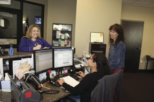 <p>Kerrville CFO Amy Dozier, right, consults with Utility Billing Clerk Crystal Juarez, seated, and Utility Billing Manager Kesha Franchina, in their City Hall offices.</p>