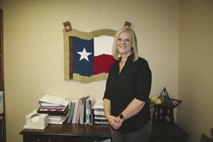 <p>Kerr County Treasurer Tracy Soldan stands by some of her work and a wall-hanging. She says she cut out the pieces, and her mother, Kathy Farrell, sewed them together, so she would have a Texas flag for her courthouse-basement office.</p>