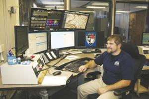 <p>Travis Trimble, KPD telecommunications specialist, during one of his 12-hour shifts at his 911 call center workstation, watches six computer monitors and listens to about 16 radio channels, handling both emergency and routine calls, and dispatches Kerr County first responders wherever they are needed.</p>