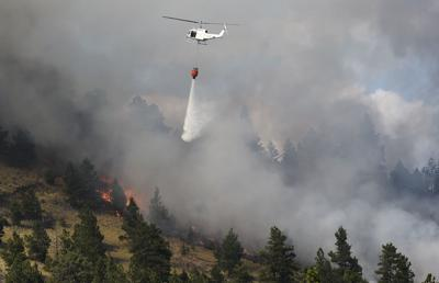 A DNRC helicopter drops water on a wildland fire that sparked Wednesday afternoon