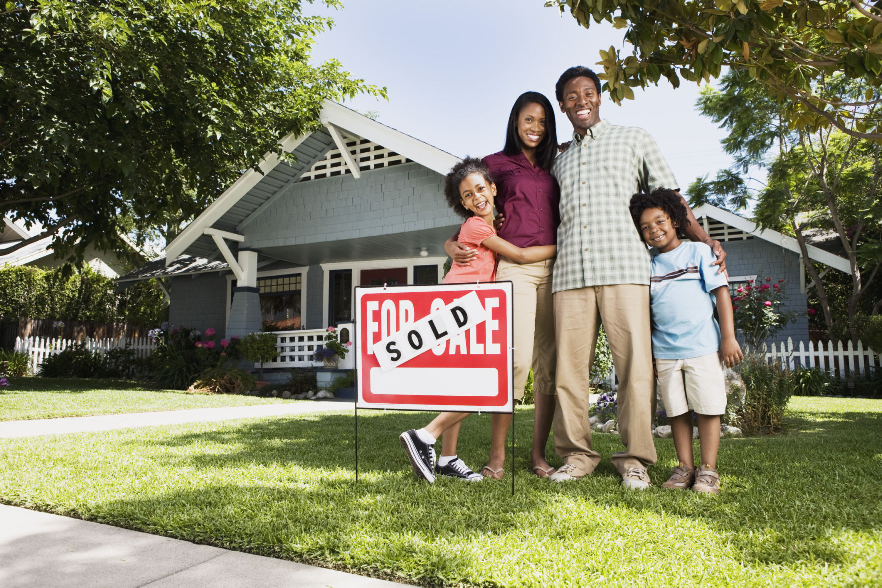 Family standing in front of house with sold sign