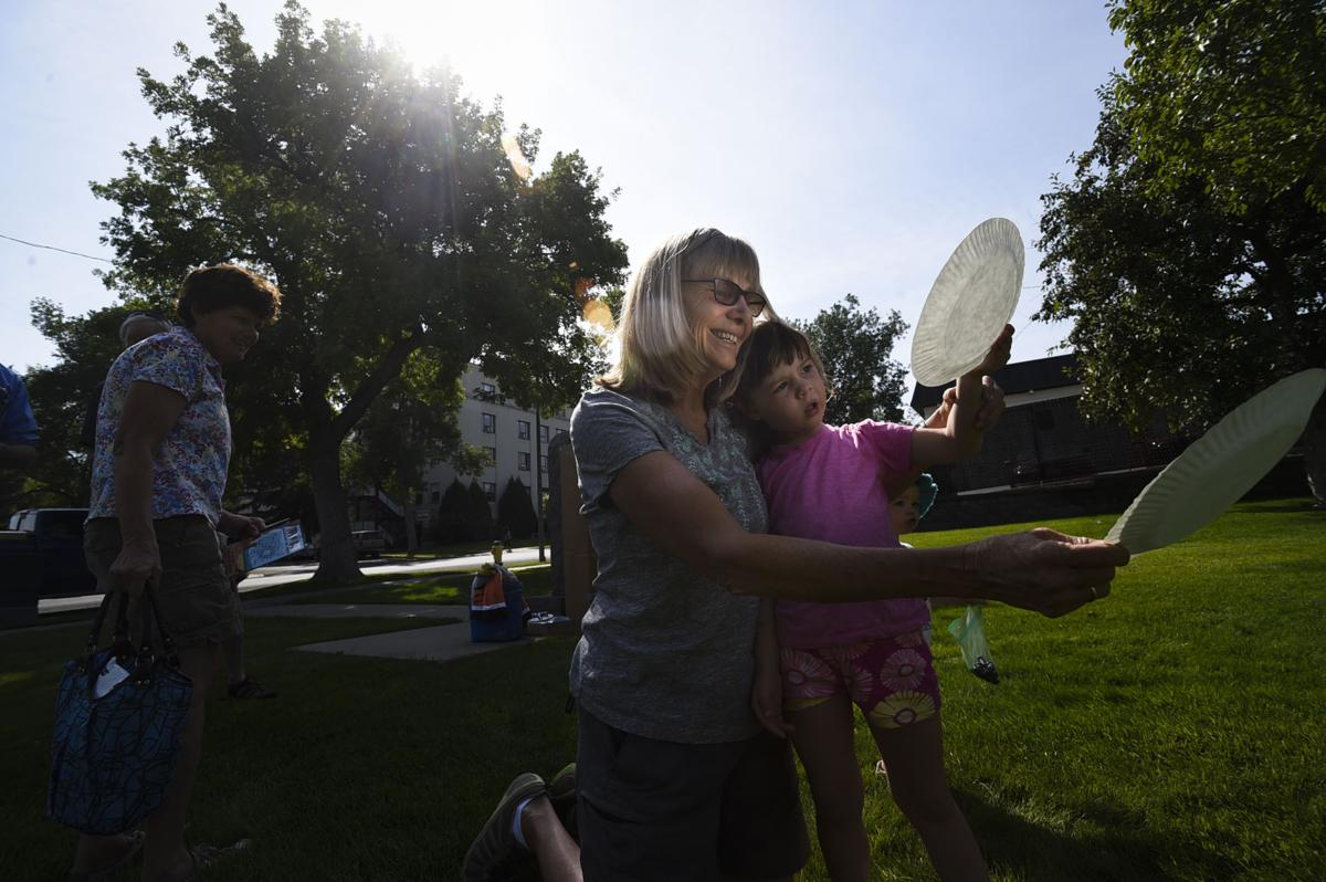 Olivia Dorrington and her grandmother Phyllis Dorrington view a projection of the solar eclipse Monday morning outside the state capitol in Helena.