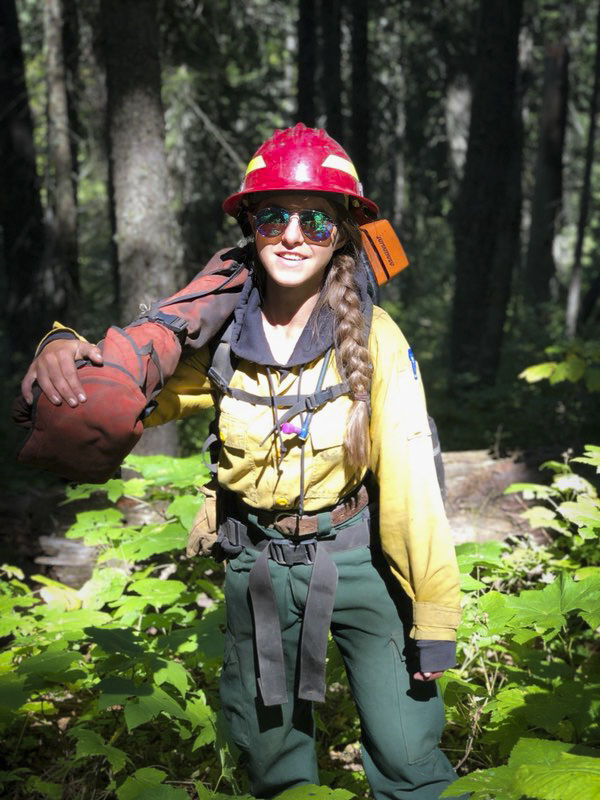 Lea Bossler carries a saw on a wildland fire.
