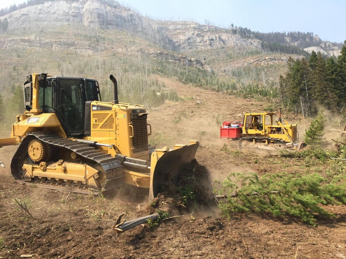 Firefighters use heavy equipment to build a fire line Wednesday while working the Alice Creek Fire which is now burning close to Highway 200.