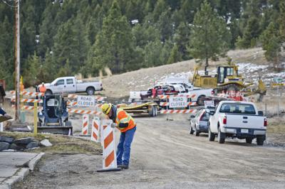 A construction worker hangs signage Monday as construction started on the new Beattie Street Trailhead.