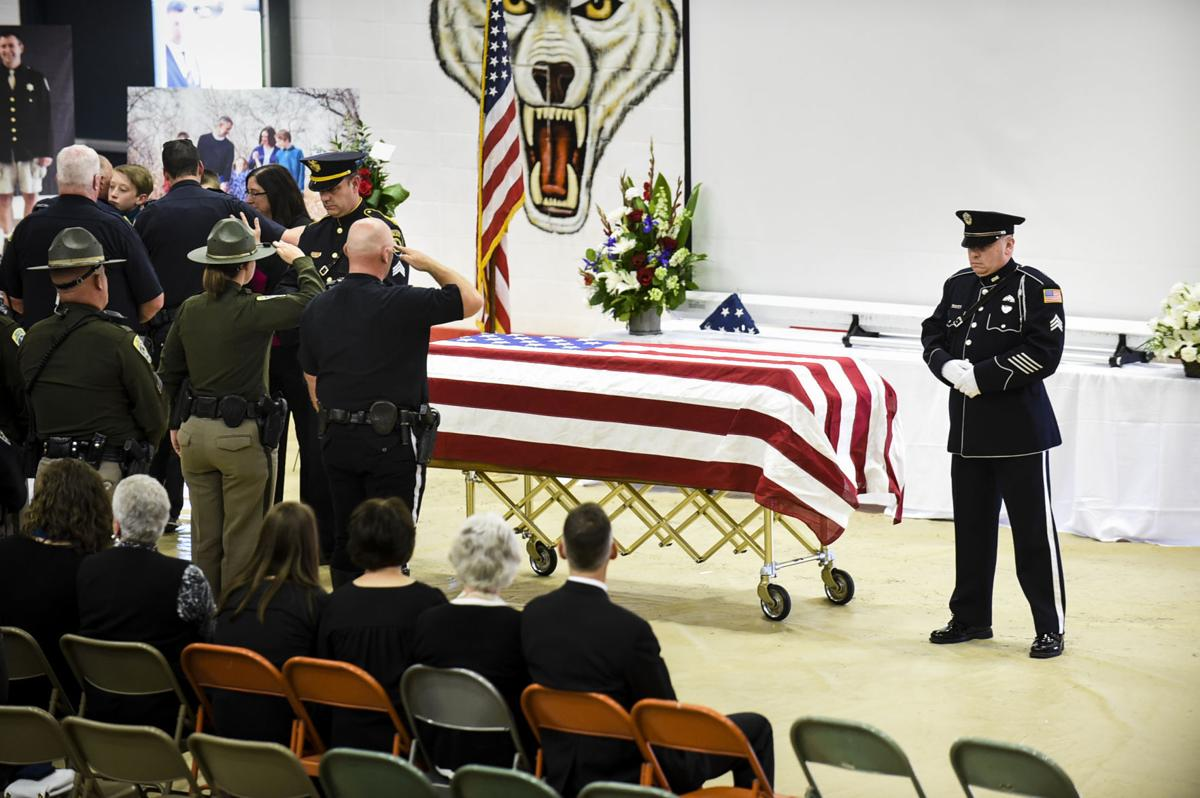 Law enforcement officers salute in front of the casket of deputy Mason Moore Tuesday afternoon.