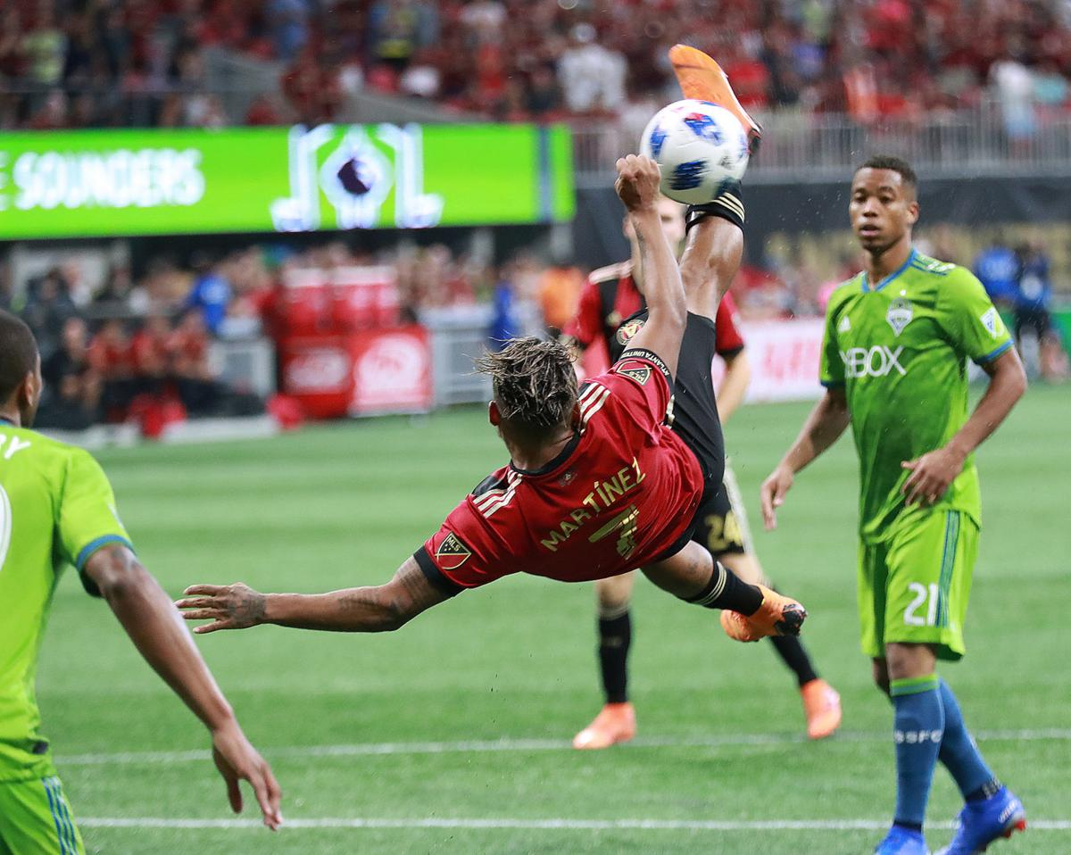 Atlanta United midfielder Josef Martinez attempts a scissor kick against the Seattle Sounders that goes wide, with Jordy Delem looking on, during the second half on Sunday, July 15, 2018, in Atlanta, Ga. Martinez scored his team's only goal in a 1-1 tie.