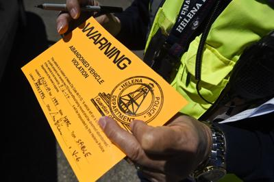 Volunteer police officer Norm Guevin prepares an abandoned vehicle violation sticker