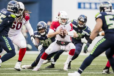 Arizona Cardinals quarterback Josh Rosen is swarmed by the Seattle Seahawks defense on December 30, 2018, at CenturyLink Field in Seattle.
