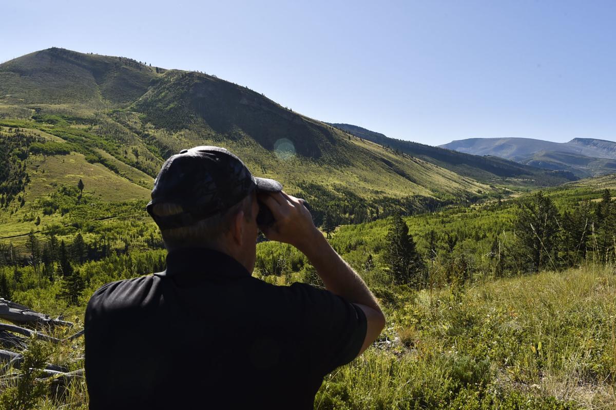 Mark Holyoak, director of communications for the Rocky Mountain Elk Foundation, looks through binoculars
