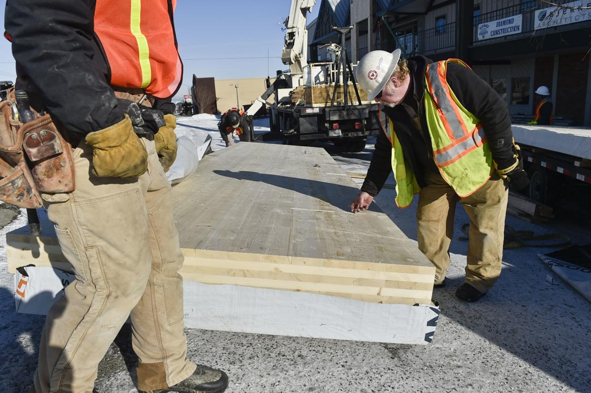 A construction worker inspects the cross-laminated timber before installing it