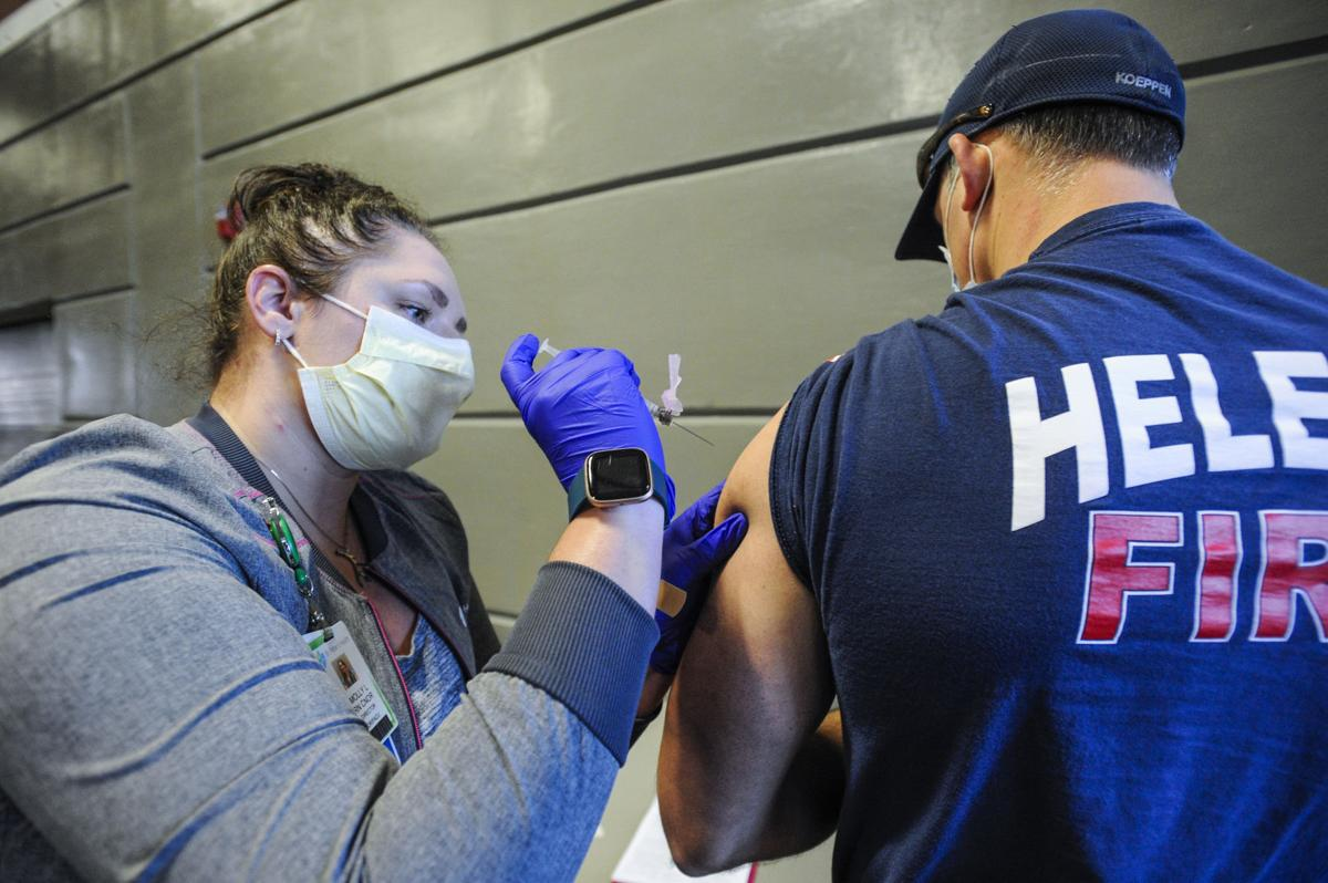 Molly Litchfield, left, vaccinates Helena firefighter Owen Koeppen