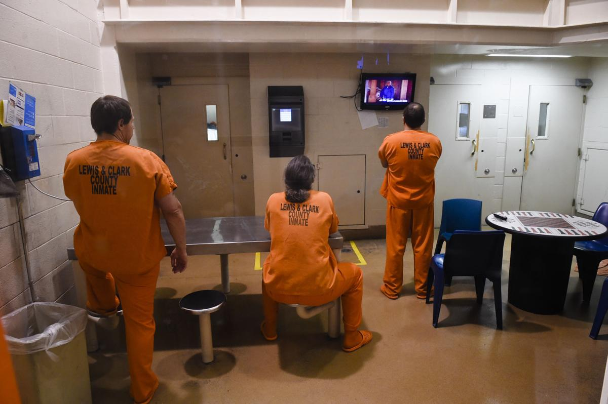 Inmates use the phone and watch television in the Lewis and Clark County Detention Center Thursday.