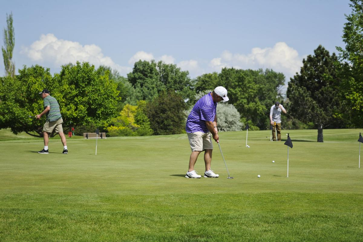 Golfers practice on the putting green