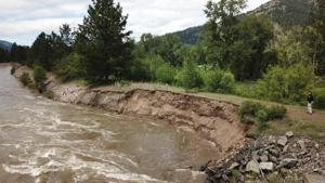 Floodwaters erode levee near Turah; possible threat to power lines, pipelines, cable