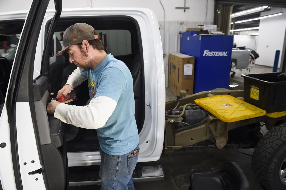 Jacob Nichols re-assembles a truck last week at Collision Pro.